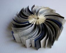 "new stage, 2012, reclaimed commercial material inserted into a folded form, 2 x 4"" closed / 2 x 8"" open"