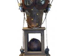 Azazel's Wife, 2007, wood construction, canvas head, headphones, chain, photo, leather mask, map pins, vials, metal parts, croquet ball, insect, number card, farm implement, curtain tie, glass, 26 x 9 x 9""