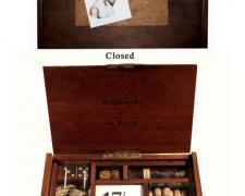 Compliments of the Season, 2007, wood box, lens, dice, vials, cork, darts, watch, paper, glass, 6 x 10 x 1 1/2""