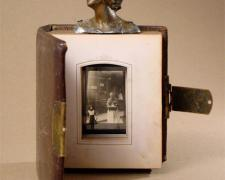 Calcutta 2006 Assemblage - leather bound photo album, head from cast metal figurine, glass lantern slide 9 x 8 x 8""