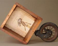 The Short Life of Karl Heck 2006 Assemblage - wood box, piano wheel, book pages, squirrel skull 11 1/4 x 16 1/2 x 5 3/4""