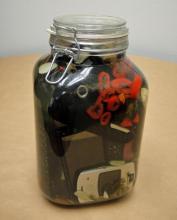 "Preserves, 2013, jar of pickled cell phones, vinegar, pepper, garlic, salt, and spices, 10 x 6 x 6"""